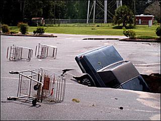 Carro afunda-se no parque de estacionamento