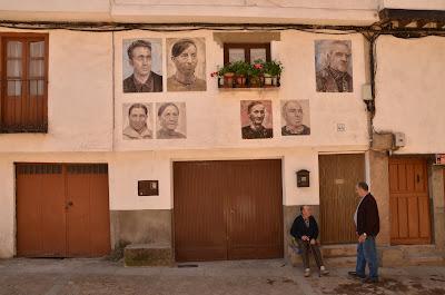 retratos sobre una fachada en Mogarraz