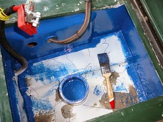 Painting metal container to prevent rust.