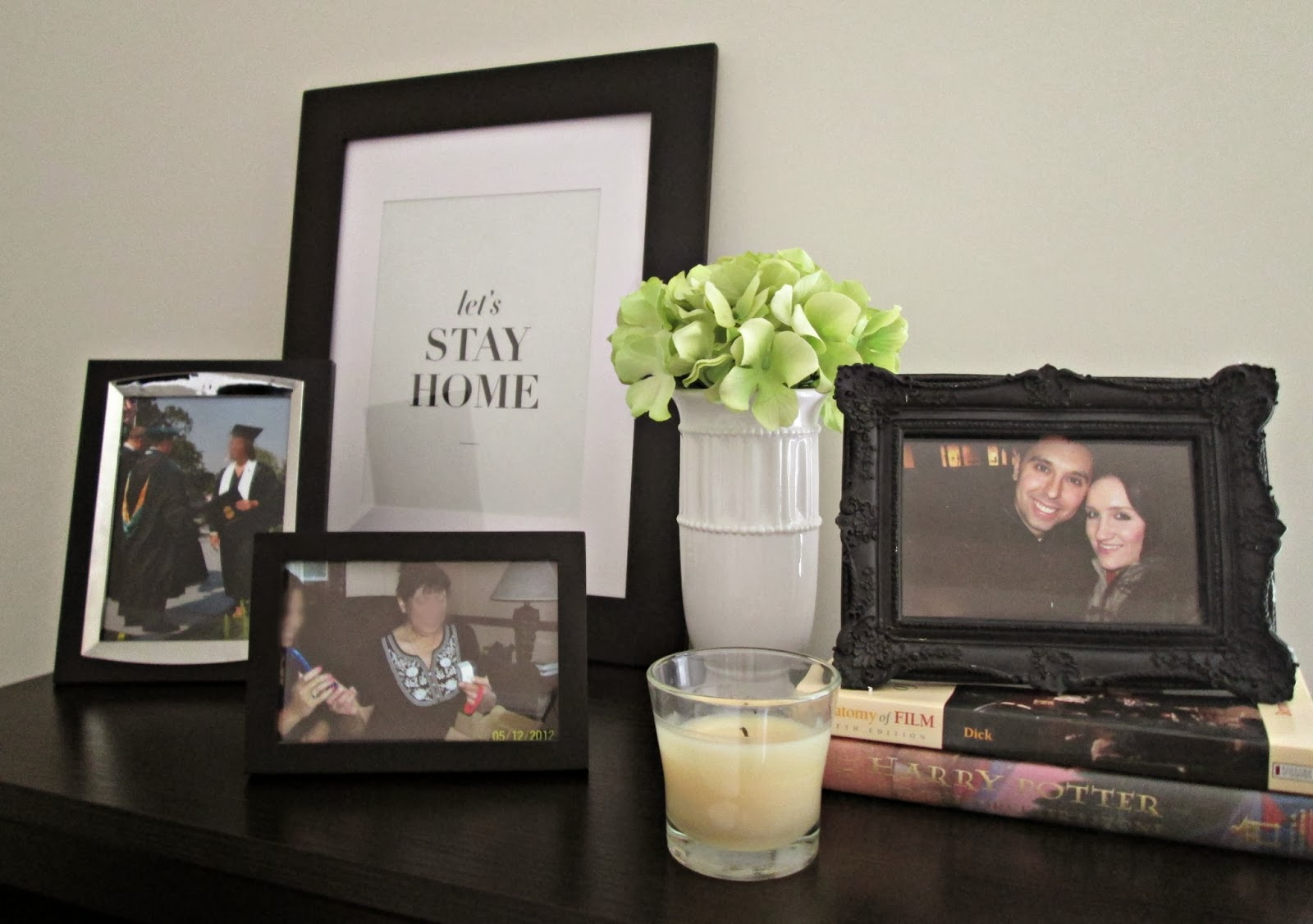 Bookshelf decor featuring picture frames, books, candles and flowers.