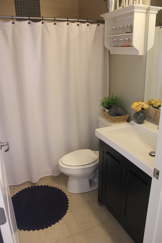 some gray towels and a purple bath mat, and the bathroom was done title=