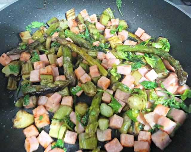Espárragos, perejil, jamón cocinándose en la sartén