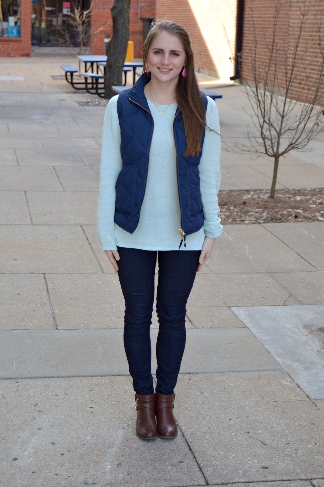 navy puffer vest over a mint sweater