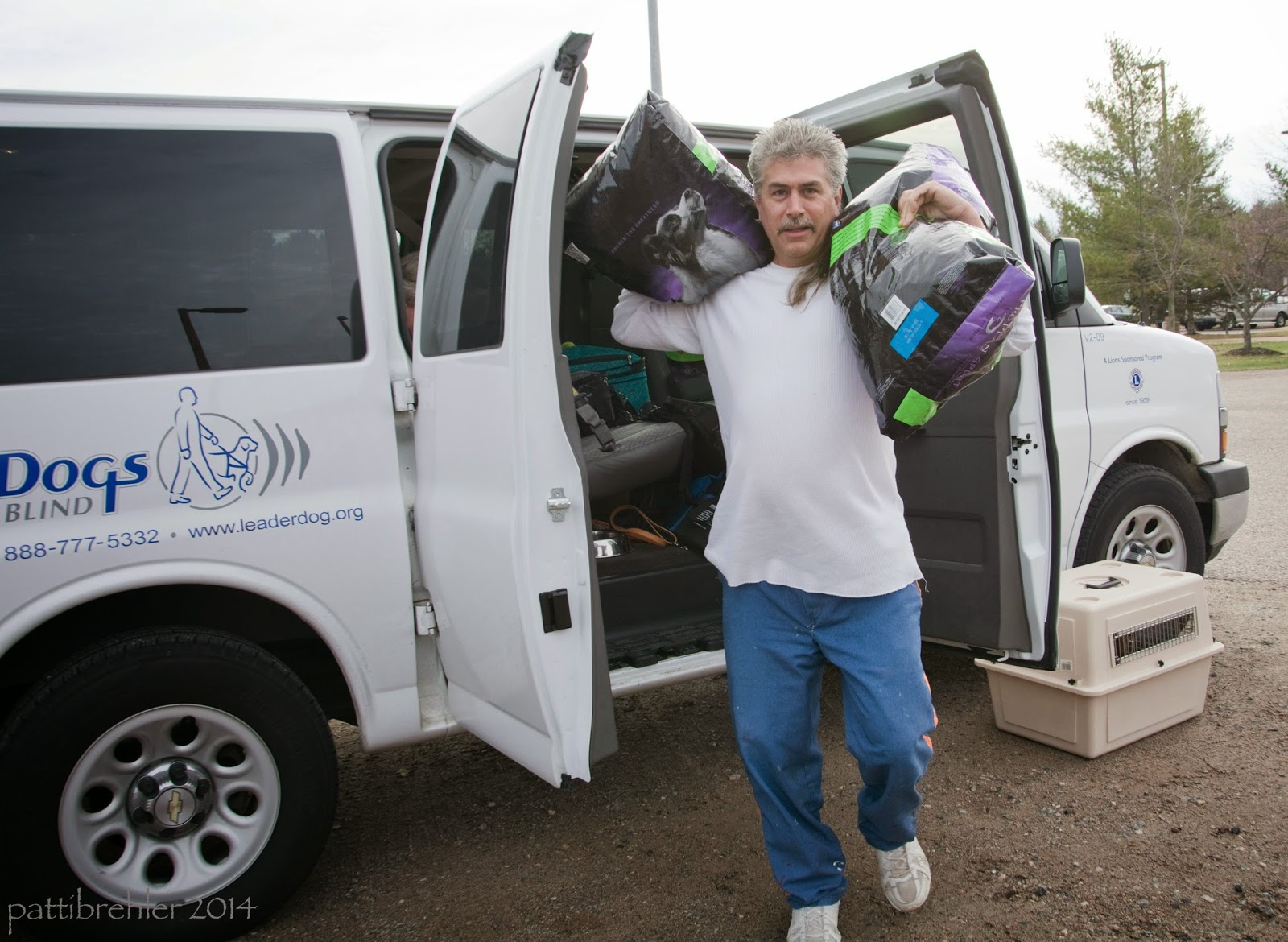A man wearing a white t-shirt and blue prison pants is facing the camera holding two large bags of dogfood, one on each shoulder. He is stepping forward away from the two open side doors of the large white Leader Dogs for the Blind van. There is a small dog airline crate on the ground next to the front tire of the van ont he right side.