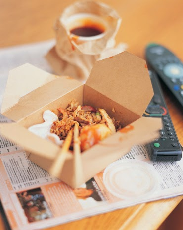 Chinese food in a brown box with chopsticks sticking out.