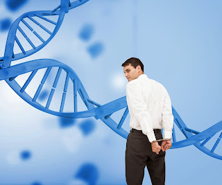 A man in handcuff stands in front of a depiction of a gene.