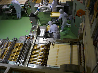 Production line at shiroi koibito biscuit factory with a worker hurrying with a stick
