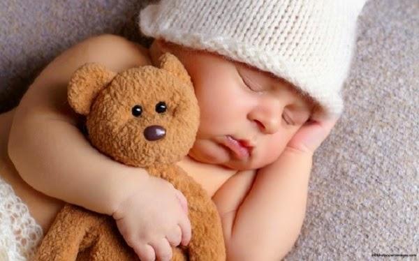 Adorable bébé qui dort avec doudou