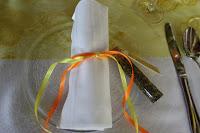 Servietten mit bunten Bändern und Gewürzmischungen als Gastgeschenk
