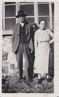 man with mustache and hat standing by a woman