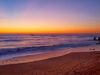Das Bild zeigt einen Sonnenuntergang im Meer, vom Strand aus betrachtet.