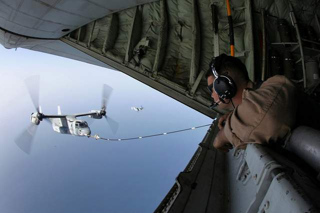 A KC-130J load master watches a refueling of an MV-22B Osprey during a training mission in 2012. (Cpl. Michael Petersheim/US Marine Corps)