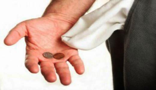 Uma mão com algumas moedas simbolizando a falta de dinheiro de uma pessoa.
