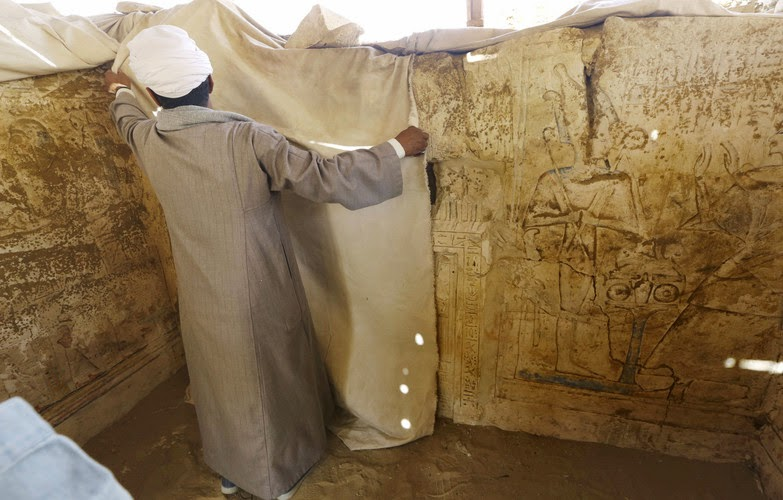 An Egyptian archeology worker covers limestones at a newly-discovered tomb dating back to around 1100 B.C. at the Saqqara archaeological site, 30 kilometers (19 miles) south of Cairo, Egypt, Thursday, May 8, 2014