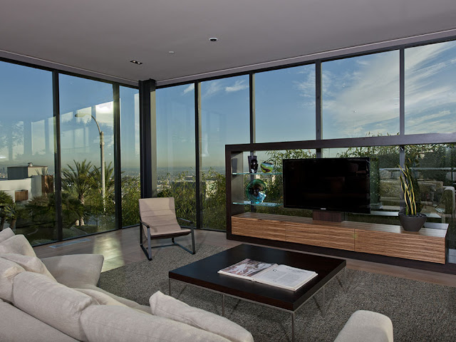 Photo of modern living room furniture by the windows with the city view