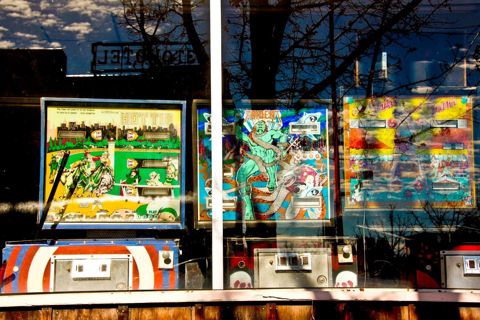 A window display of broken pinball machines and a reflection on the window of a hotel sign and a tree.