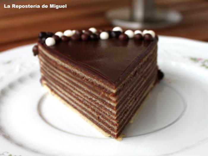 Foto frontal de la porción de pastel, presentado en un plato blanco de porcelana con ramillete de flores. El pastel esta decorado alrededor con bolas de tres chocolates.Se aprecia perfectamente las diferentes capas del bizcocho, hasta 20 capas llaga a tener.