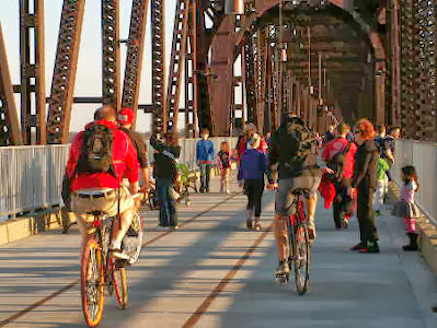 many people walking and some on bicycles going across the big four bridge