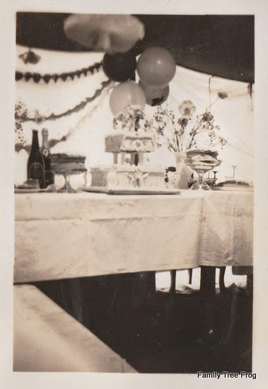 picture of cakes on trestle tables covered with sheets.  Balloons, streamers and gum trees in background.