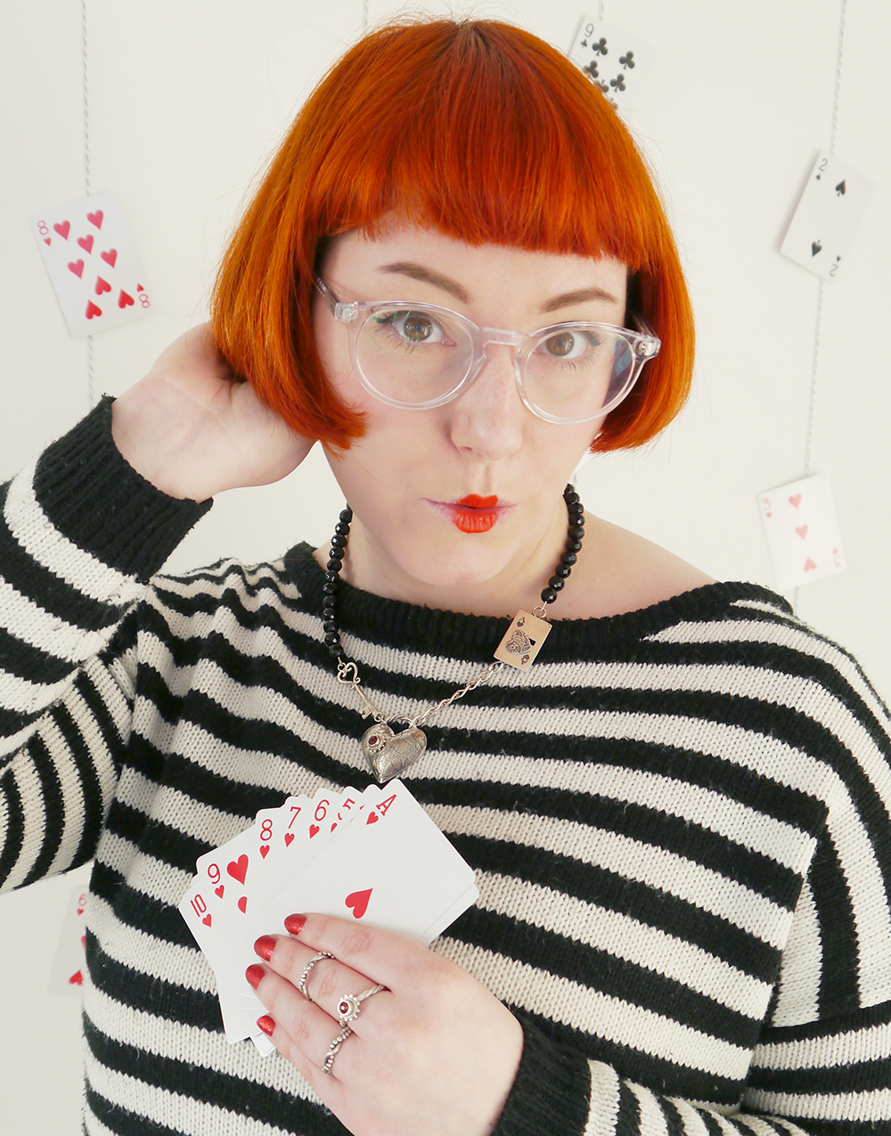 Queen of Hearts, Alice in Wonderland, Queen of Hearts outfit, red queen, literary style, Karen Smith jewellery, heart jewellery, Dundee jewellery, Dundee design, Scottish jewellery design, red  hair, dinger, Scottish blogger, pack of cards, Iolla glasses, clear glasses, red lips, doll lips, stripey jumper, gold skirt, red glitter hearts