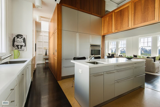 Kitchen in a NYC penthouse with dark wood floor, white cabinets with long silver drawer pulls and stainless appliances