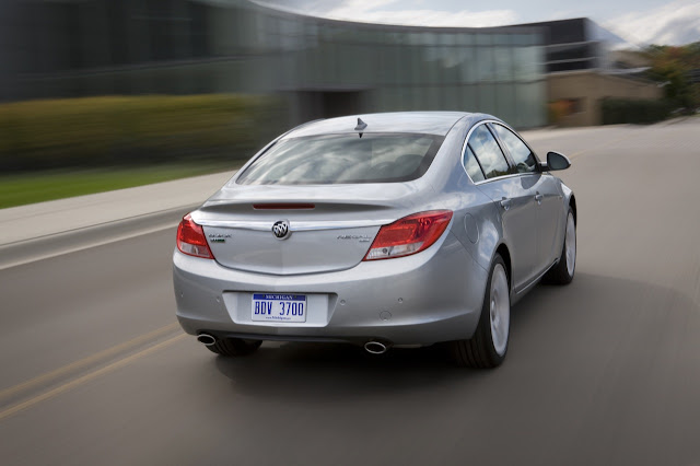 Rear 3/4 view of silver 2011 Buick Regal driving on city street