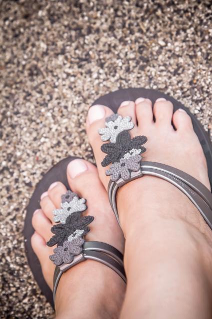 Füße mit Ipanema Sandalen in schwarz mit Blumen und Nude Nagellack