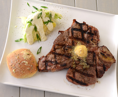 grilled steak, wedge salad, garlic roll, grilled t-bone, steak with compound butter
