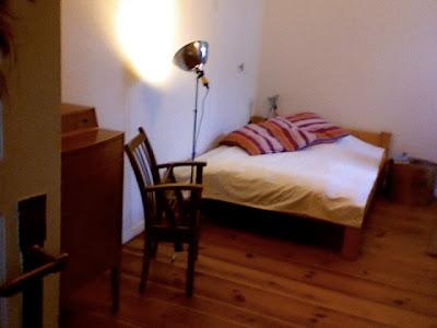 Ein Schlafzimmer mit weißer Tagesdecke, Holzmöbeln und -dielen