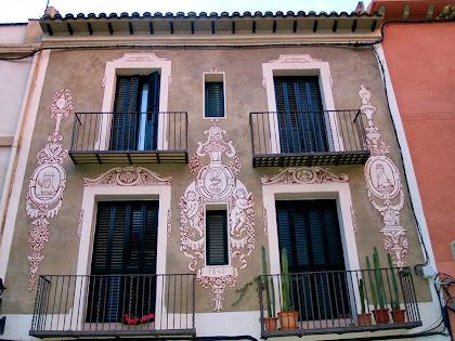 Façana de l'antiga Farmàcia Bujons esgrafiada per Ferran Serra el 1954, amb dibuixos referents a la farmàcia i una cinta amb la data 1842