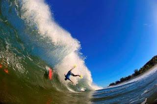 Homem caindo na onda do mar