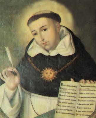 Santo Tomas de Aquino con el libro abierto y la pluma en la mano.