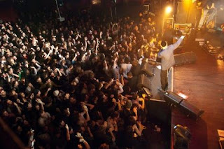 Screen shot image of the band playing live in front of large crowd