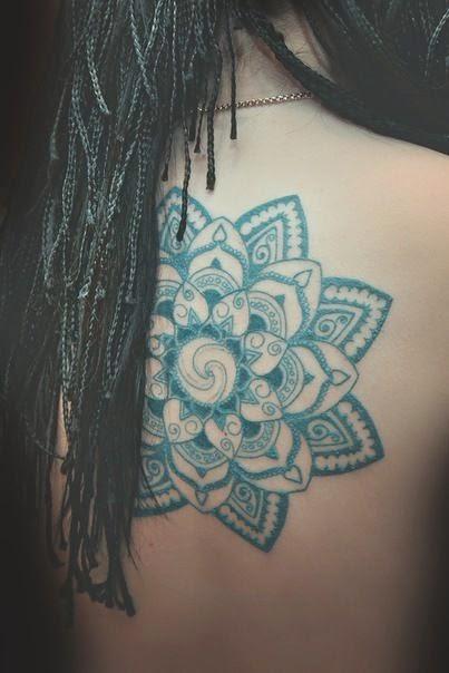 Chica con tatuaje hindu en la espalda