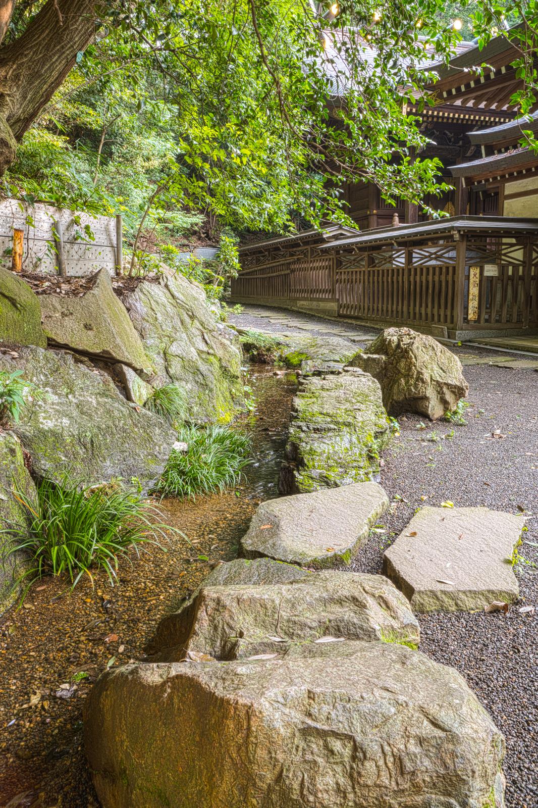 貫井神社の玉垣と湧水の水路の写真