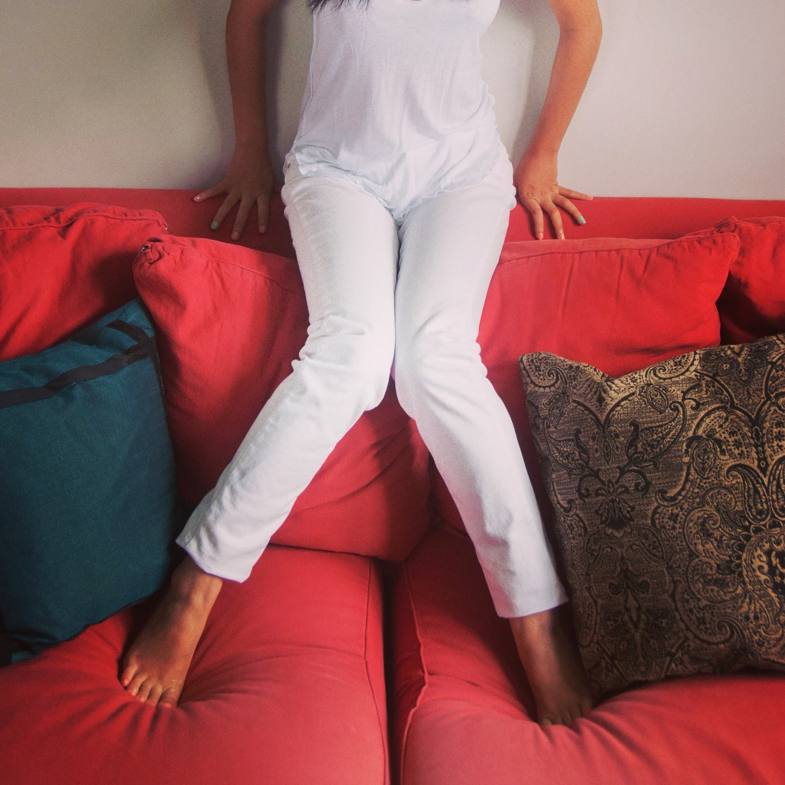 white pants white tank red couch cushions