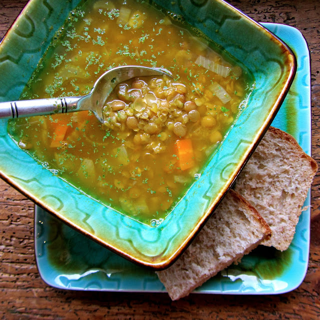green ceramic bowl with lentil soup in it and sliced homemade bread on the side