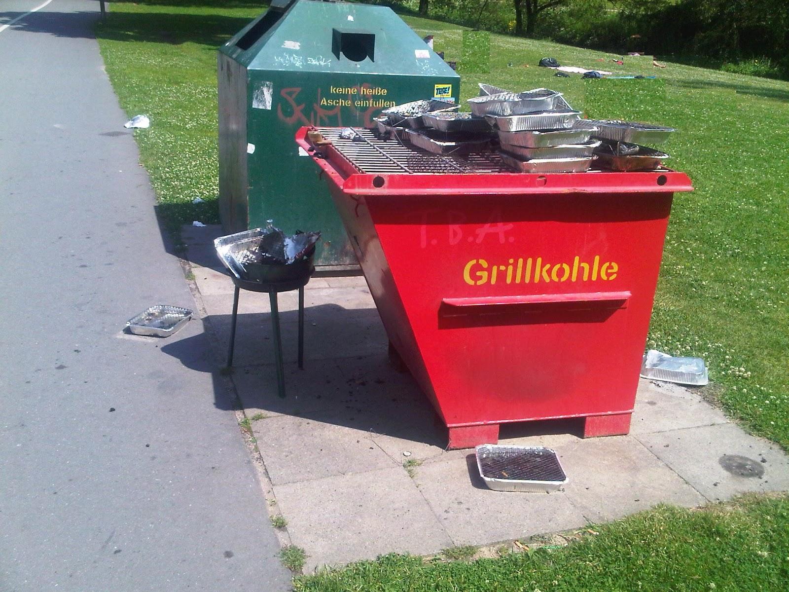 Roter Grillkohle-Müllcontainers mit vielen Aluschalen-Grills oben drauf als Müll im Park an einem geteerten Radweg.