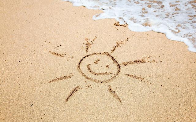 Tekening van een zon in het zand op het strand