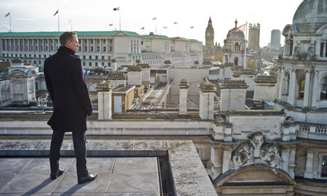 Daniel Craig as James Bond standing on a roof in Skyfall movieloversreviews.blogspot.com