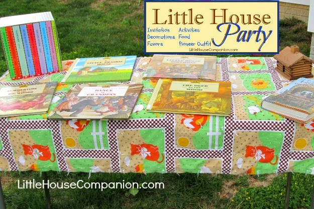 Little House books displayed on a quilt for party.