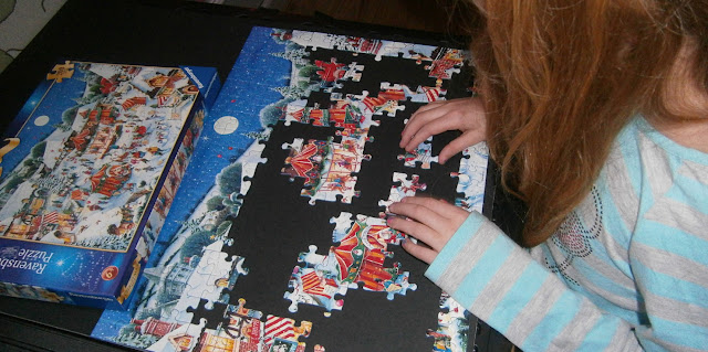 child completing Christmas jigsaw puzzle