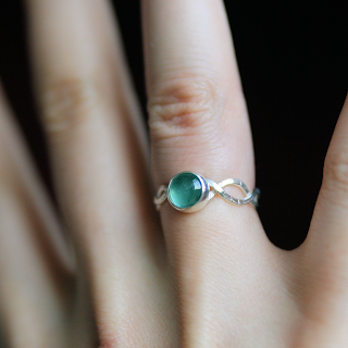 Silver sea-green tourmaline wave ring on finger