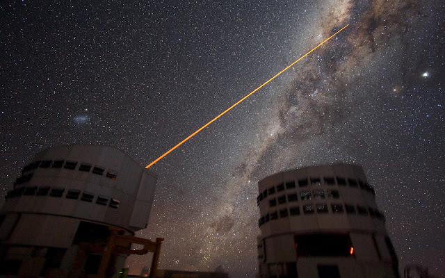Shooting a Laser at the Galactic Centre The sky above Paranal on 21 July 2007. Two 8.2-m telescopes of ESO's VLT are seen against the wonderful backdrop of the myriad of stars and dust that makes the Milky Way. Just above Yepun, Unit Telescope number 4, the Small Magellanic Cloud - a satellite galaxy of the Milky Way - is shining. A laser beam is coming out of Yepun, aiming at the Galactic Centre. It is used to obtain images that are free from the blurring effect of the atmosphere. On this image, the laser beam looks slightly artificial. This is a side effect due to saturation caused by the long exposure time. Planet Jupiter is seen as the brightest object on the upper right, next to the star Antares. Image taken by ESO astronomer Yuri Beletsky.  Image Credit: ESO/Yuri Beletsky Explanation from: http://www.eso.org/public/images/eso0733b/