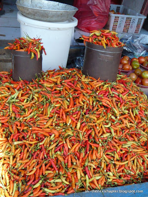 Market stand with lots and lots of hot chillies in different colours, the colour of fire.