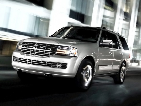 Silver 2011 Lincoln Navigator front 3/4 view driving on city street at night