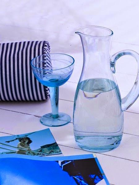 Niebieski dzbanek z wodą i kieliszkiem na plaży
