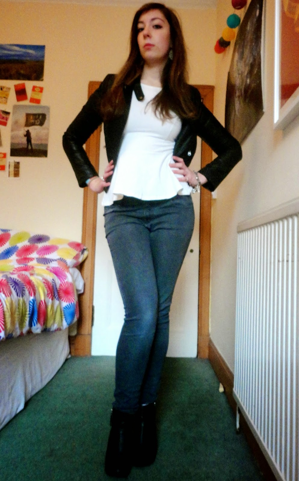 Outfit of black leather jacket, white peplum top, grey skinny jeans & black heeled ankle boots