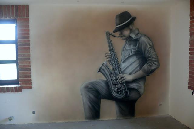 Malowanie na ścianie murala w czarno-bieli, motyw jazzowy, malowanie saksofonisty w pokoju młodzieżowym, pokój młodzieżowy, grafitti 3D