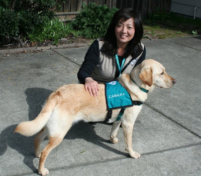 cabana and i in our driveway, she has on her teal vest for therapy, i am wearing a fleece vest with therapy dog logo